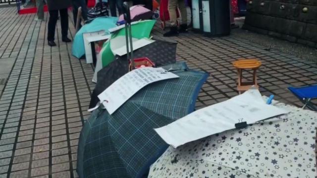 お見合い広場に並んだ雨傘。結婚を希望する人の身長や職業などを書いたメモが貼られている
