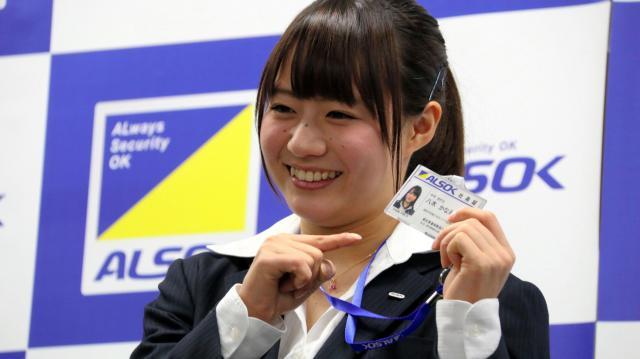 4月に入社した綜合警備保障の社員証を手に、笑顔を見せる八木さん=綜合警備保障提供