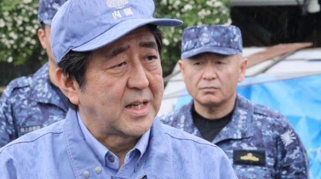 熊本の被災地を視察後、報道陣の質問に答える安倍晋三首相。右は河野克俊統合幕僚長=2016年4月23日、熊本県益城町