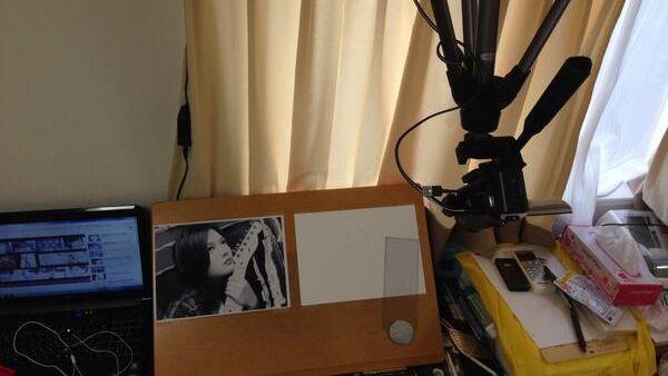 自宅で、白黒の写真を参考にしながら描いている。天井からカメラをぶら下げ、動画撮影も=古谷さん提供