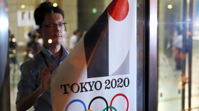 都庁の玄関で、佐野研二郎氏がデザインした東京五輪のポスターをはがす都職員=2015年9月1日、東京都新宿区、関田航撮影