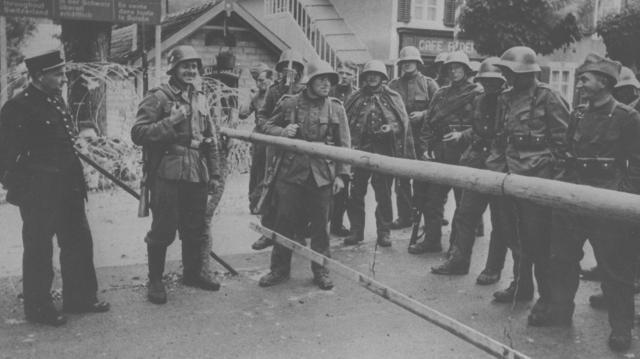 1940年7月、スイス・フランス国境で相対するスイス警備兵(右)とドイツ兵(中央)とフランス税関吏(左端)