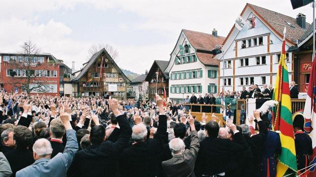 直接民主主義をとるスイス。アッペンツェル・インナーローデン州であった青空議会のために広場に集まった州民と議事を進める州幹部(手前)=2004年4月25日