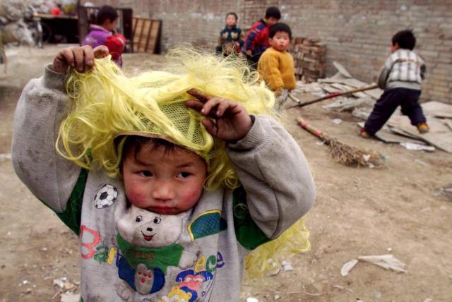 1999年2月北京。出稼ぎ労働者の親のそばにいながら、学校へ通えない子供たち。