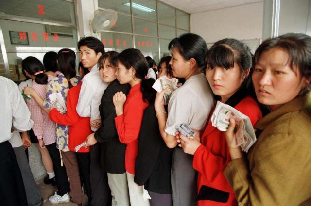 1999年3月、広東省番禺。家族に仕送りをする出稼ぎ労働者たち。