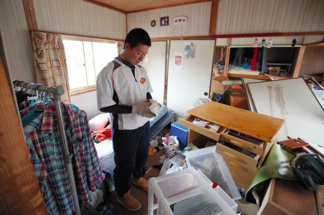 散乱した自分の部屋で、中学校の野球部コーチからメッセージが入った卒業記念ボールを見つけた高3生の後藤海斗くん(17)。高校は休校中で練習も出来ていない。「最後の夏。大会には出たい」=4月18日午前10時16分、熊本県南阿蘇村、遠藤啓生撮影