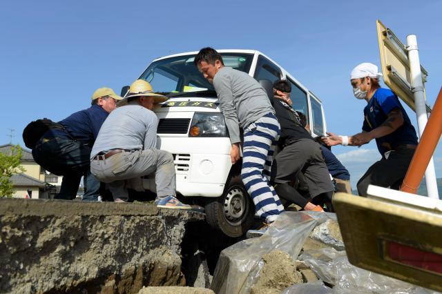 ガス復旧のために被災地を走行していた軽自動車が、アスファルトの割れ目にタイヤを落としてしまい動けなくなった。近くにいた男性が「誰か来いや!」と叫ぶと、ボランティアで民家の片付けのため鹿児島から来ていた若者らが集まり、車を押し上げた=4月17日午後3時56分、熊本県益城町、加藤諒撮影