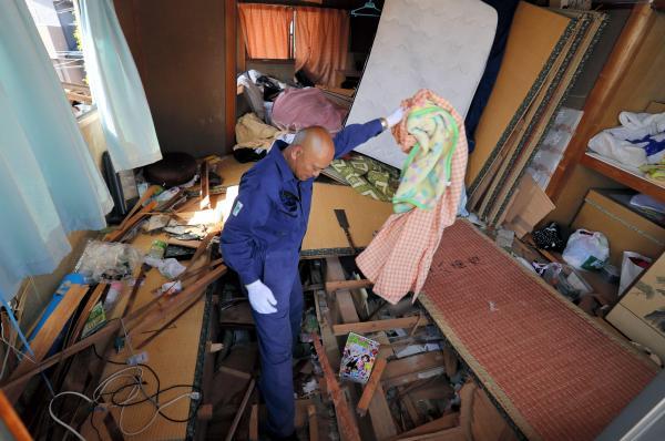 1階部分が押しつぶされた妻の実家に入り、必要な物がないか探す永田裕昭さん(43)。16日の本震後、初めて中に入り、パソコンや衣類などを運び出した。14日の前震で、1階にいた妻の両親は家具や潰れた2階部分に挟まれ、救助隊に救助された。16日の本震で家はさらに傾いたという。永田さんは「救助隊が来る前、畳などをのこぎりで切ったりして救助を手伝った。命があって何より