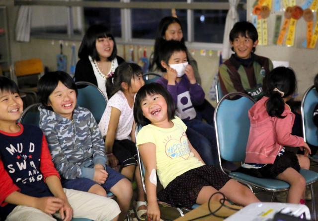 夜、寝る前にアニメ映画を見て笑う子どもたち。余震への恐怖を少しでも和らげたいと企画された=4月19日午後7時27分、熊本市中央区の白山小学校、細川卓撮影