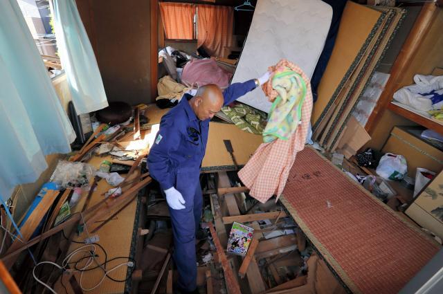 1階部分が押しつぶされた妻の実家に入り、必要な物がないか探す永田裕昭さん(43)。4月16日の本震後、初めて中に入り、パソコンや衣類などを運び出した。14日の前震で、1階にいた妻の両親は家具や潰れた2階部分に挟まれ、救助隊に救助された。16日の本震で家はさらに傾いたという。永田さんは「救助隊が来る前、畳などをのこぎりで切ったりして救助を手伝った。命があって何よりです」と話していた=4月22日午後2時17分、熊本県益城町、西畑志朗撮影