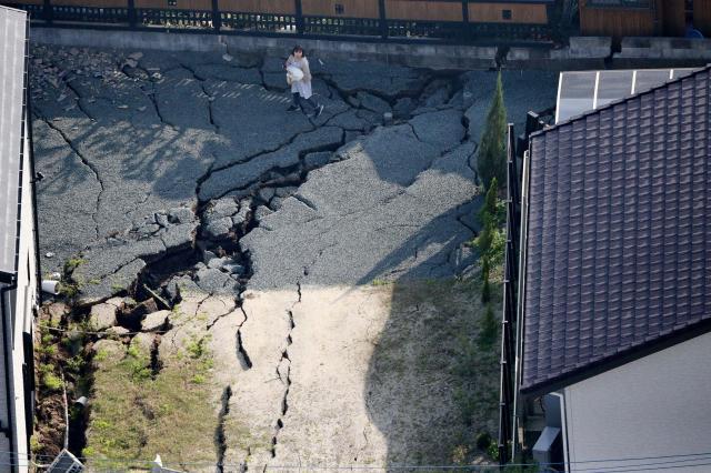 敷地に入った大きな亀裂の横で赤ちゃんを抱いて上空を見上げる女性=4月15日午前7時55分、熊本県益城町、朝日新聞ヘリから、森下東樹撮影
