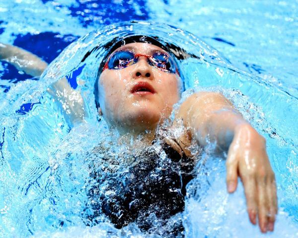 中学3年生で五輪出場を決めた酒井夏海選手。競泳の日本選手権、200メートル背泳ぎ準決勝のターン後の浮き上がりで、水が顔の周りに膜を張ったように見えた=4月9日、東京辰巳国際水泳場、西畑志朗撮影
