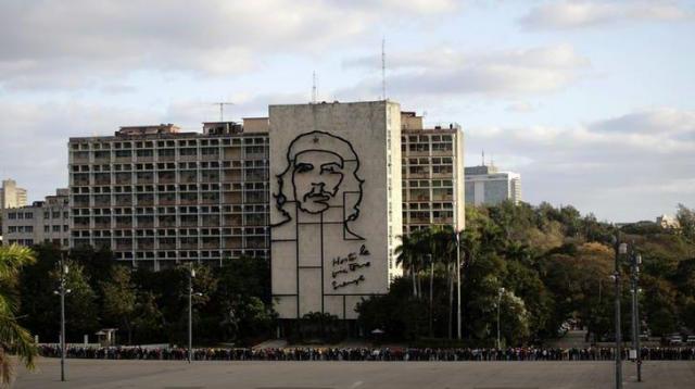 キューバ革命の英雄チェ・ゲバラの顔が壁に描かれたキューバの内務省のビル。夜はライトアップされる