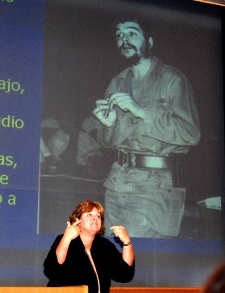 父の写真を背に語るアレイダ・ゲバラさん。「広島に行き、大きな痛みを感じた。父は『起こってしまったことに抗議するだけでは不十分。二度と繰り返さないようにせねばならない』と語っていた」と講演した=広島市立大