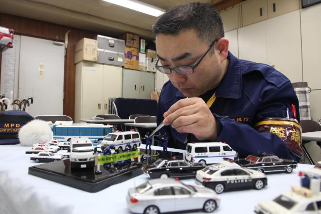 捜査車両の模型や鑑識課員の人形を並べる小沢伸行さん=東京都千代田区の警視庁