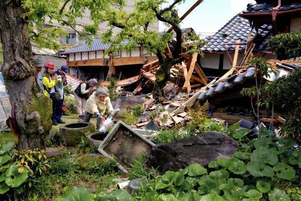 地震で倒壊し、住んでいる人が亡くなった家の前で手を合わせるボランティアや近所の住民ら。尾方勝子さん(71・右端)は「今日は暑いから」と水が入った石に花を供えた。故人は花が好きで庭を美しく飾っていたという=22日午前、熊本県益城町、福岡亜純撮影