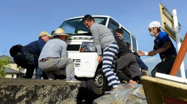 動けなくなった軽自動車。近くにいた男性が「誰か来いや!」と叫ぶと、ボランティアの若者らが集まり、車を押し上げた=4月17日午後3時56分、熊本県益城町、加藤諒撮影