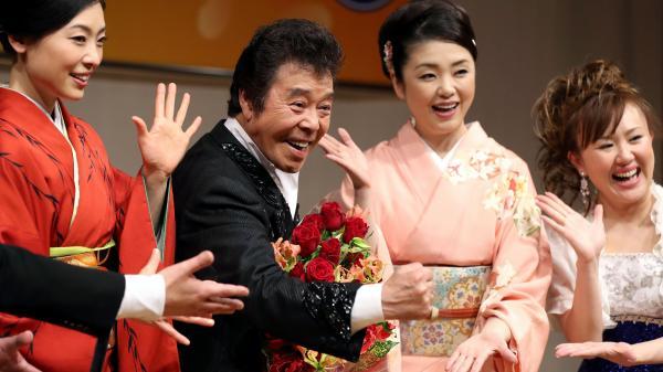 仲間から結婚を祝福される演歌歌手の冠二郎さん(左から2人目)=東京都渋谷区、長島一浩撮影