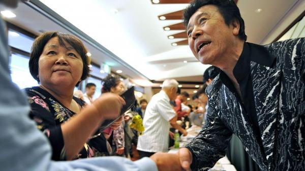 ファンと握手する冠二郎さん=2012年9月30日
