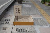 鳥取県が歩道のくぼみに設置した「砂かけ婆の砂」看板。反響が大きく、31日に撤去された