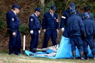 逃走の末、死んだシマウマ「バロン」を囲む警察官ら=3月23日、岐阜県土岐市