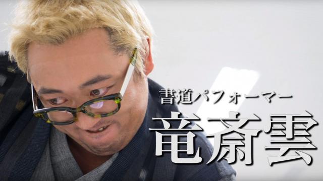 書道パフォーマーに扮した秋山さん。書道なのに金髪を選ぶところが「いかにも」