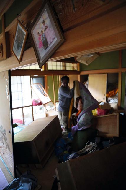 家具が散乱した自宅に戻り、避難所で使う布団や座布団を家から運び出す住民。お願いして家に上がらせてもらった=4月16日、熊本県西原村、金川雄策撮影