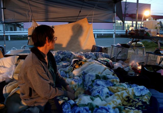 認知症と糖尿病を患う88歳の母と路上で夜を過ごしていた武久成美さん(手前)。家は余震の度に「ミシッ」と音を立てるという。おむつ交換のほか、多くの医療用の器具を持ち込む必要があるため「避難所に入ろうにも、まわりに迷惑をかける」という。16日は雨の予報が。「雨が降る前に、母を介護しながら住めるアパートに移りたい」と話した。この写真は1面に掲載された=4月15日、熊本県益城町、金川雄策撮影
