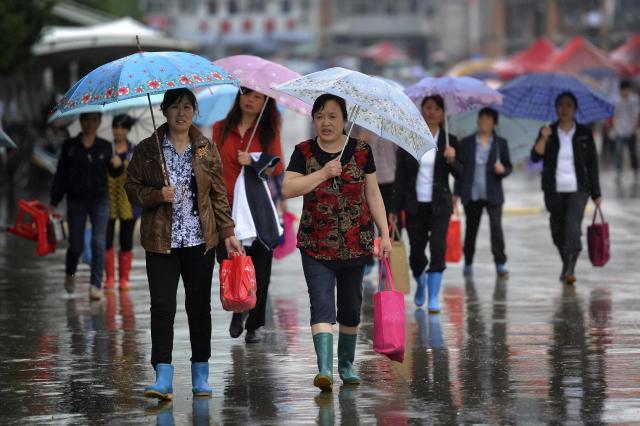 雨のなか、子どもたちに弁当を届ける母親たち=安徽省、2012年6月