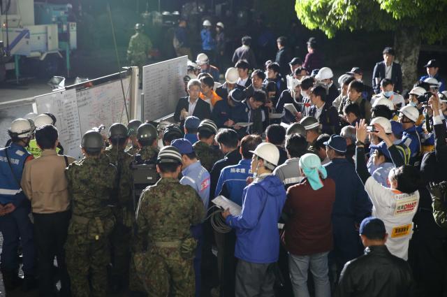 東京から熊本県益城町役場に到着し、一番最初に撮影した写真。地震被害が大きかった庁舎の外で、関係者が被害情報を共有していた=4月15日午前5時4分、金川雄策撮影