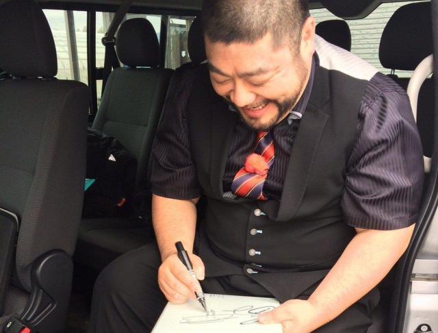 笑顔でサインに応じる髭男爵の山田ルイ53世さん