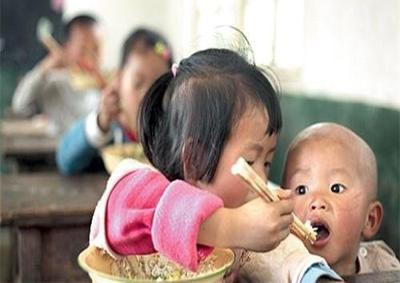 フリーランチの給食を、弟に分け与えている小学生=2011年、湖南省新晃侗族自治県大坪坡村