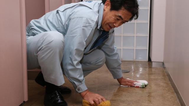 超党派議連「国会掃除に学ぶ会」の活動の一環で国会内のトイレで床を磨く逢沢一郎氏=2014年11月19日、越田省吾撮影