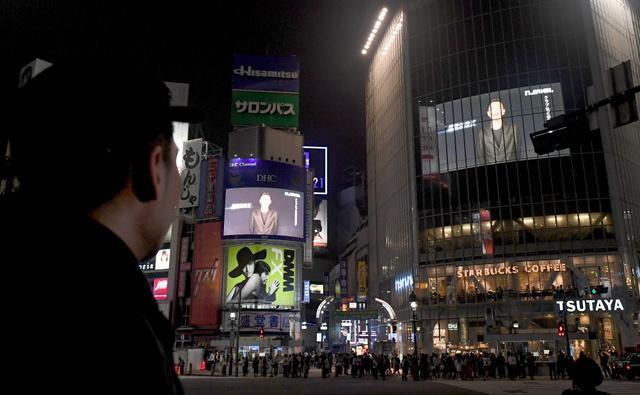 JR渋谷駅前スクランブル交差点の大型ビジョンに映し出されたメッセージを見つめるZeebraさん(左)=23日午前0時、竹花徹朗撮影