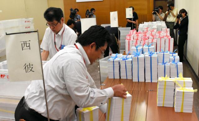 投票所入場券の発送準備作業をする長崎市と郵便局の職員=2016年6月20日、長崎市大黒町の市選挙管理委員会