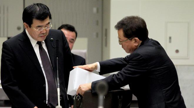 東京都議会総務委員会で、徳洲会側から受け取った5千万円を入れたとされるカバンに、札束を模した箱を入れる猪瀬直樹さん(右)=2013年12月16日、都庁