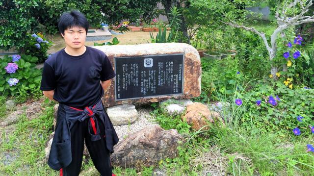 小学校跡地にある校歌の碑の前に立つ最年少の岩城保人さん(19)=三重県志摩市志摩町和具