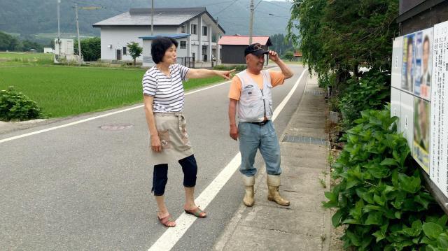 候補者ポスターが出そろった。さっそく掲示場の隣に住むご夫婦が選挙談議=岐阜県白川村荻町