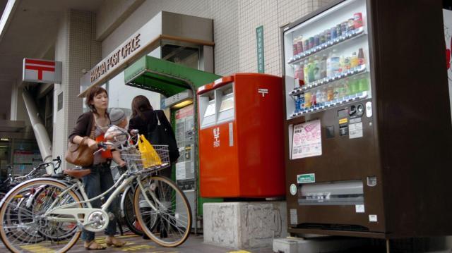 郵政民営化によって、郵便局には様々な変化が現れた。空きスペース活用のため、郵便局の入り口脇に設置された飲料の自動販売機=2005年10月14日、福岡市博多区の博多郵便局で