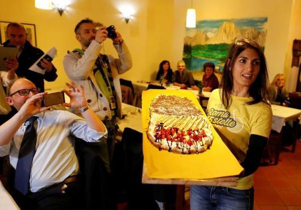 Tシャツ姿で巨大なピザを手にする、ローマ市長に選ばれたビルジニア・ラッジ氏=2016年5月24日、ロイター