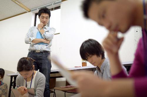 高校生とボランティアスタッフの交流を見守る今井紀明さん(左奥)=2013年3月、大阪市城東区