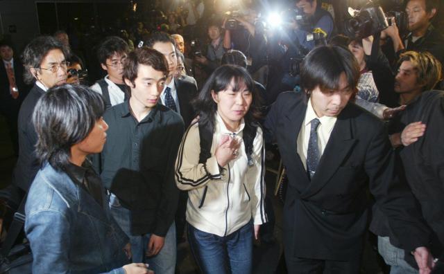 解放され帰国。足早にバスへ向かう今井紀明さんら=2004年4月18日午後、羽田空港で