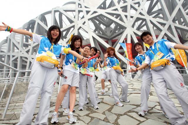 北京五輪開会式当日を迎えた8日朝、会場の国家体育場「鳥の巣」前ではボランティアが記念撮影をしていた=2008年8月