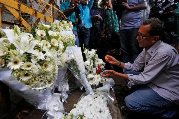 犠牲者のために花束を供える男性