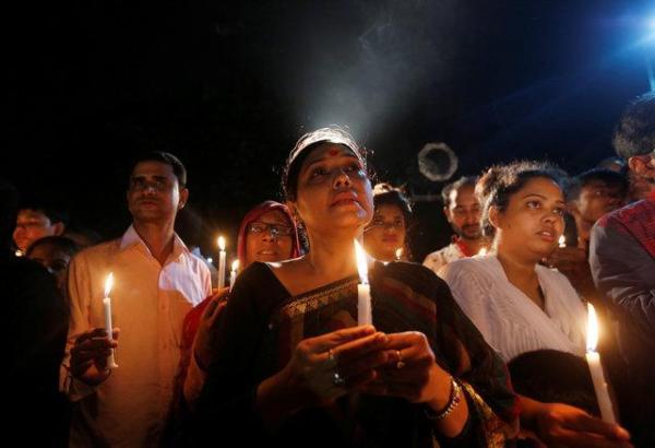 ロウソクを手に持って祈りを捧げる女性たち