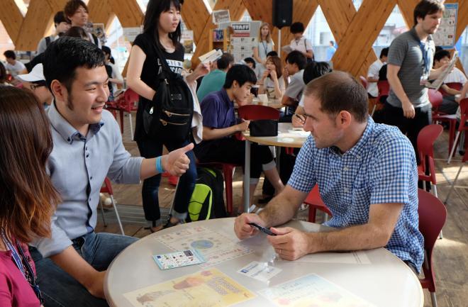 英語村のスタッフと話す山田さん。開放的なスペースは、大勢の学生らで賑わう=7月5日、東大阪市の近畿大学、西村悠輔撮影