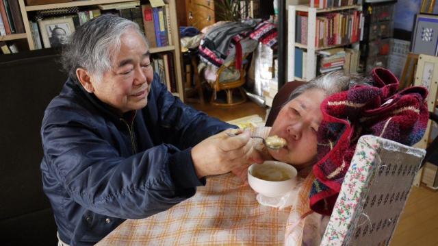 自宅で美子さんの食事を介助する孝さん