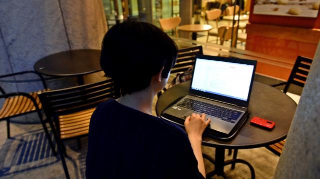 仕事帰りに求人情報をチェックする派遣社員の女性。この日は、週末の単発仕事で採用通知が届いていた=2015年6月10日、大阪市北区