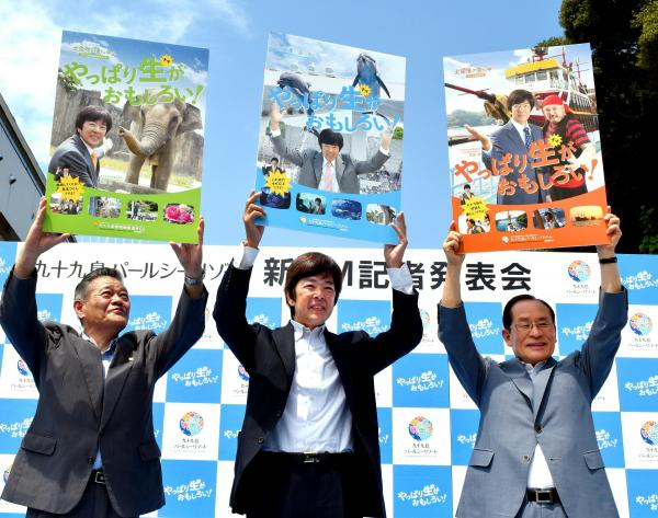 パールシーリゾートのポスターにも登場している高田明さん(中央)=7日、長崎県佐世保市鹿子前町