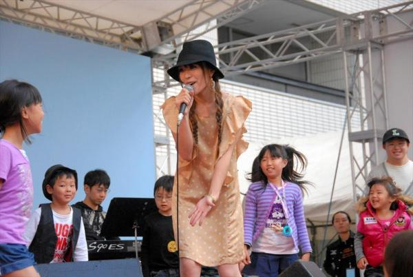 トークショー後、会場の子どもたちをステージに招き入れ、持ち歌を歌う今井絵理子氏=2011年10月16日